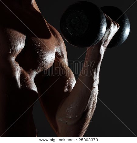 Part of a wet man's body with metal dumbbell on a gray background