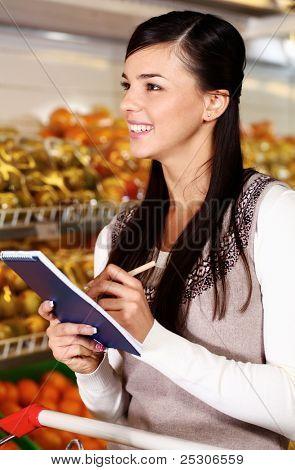 Bild der schönen Frau tickt, was sie im Supermarkt gekauft hat