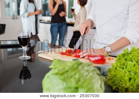 Cropped image of female cutting vegetables while friends having drink in background