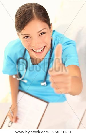 medical people. Woman nurse showing thumbs up success sign smiling happy and successful at camera. Beautiful young female nurse or young doctor with clipboard or positive medical record