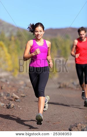 Running woman with male runner in background trail running training for marathon in volcanic landscape. Mixed race Chinese Asian / Caucasian woman jogging.