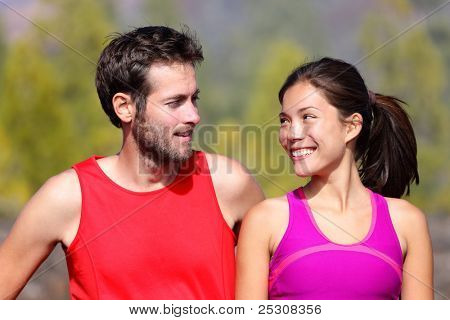 Happy sporty couple portrait. Runners outside resting after running. Man and woman smiling at each other. Asian female athlete and white caucasian male model.
