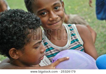 Smiling Fijian school boy holding balloon
