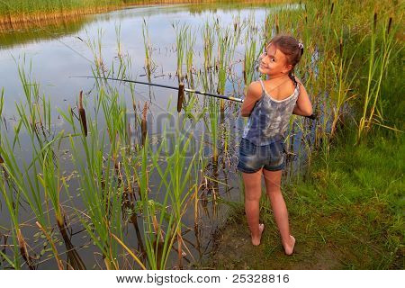 pretty young girl fishing on river in summer