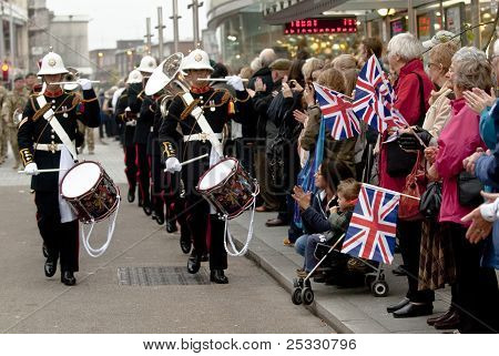As multidões animar & onda suas bandeiras Union na maching approches de banda