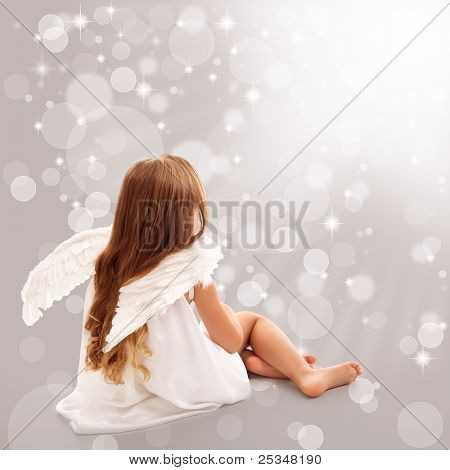 Little angel thinking in divine light while sitting
