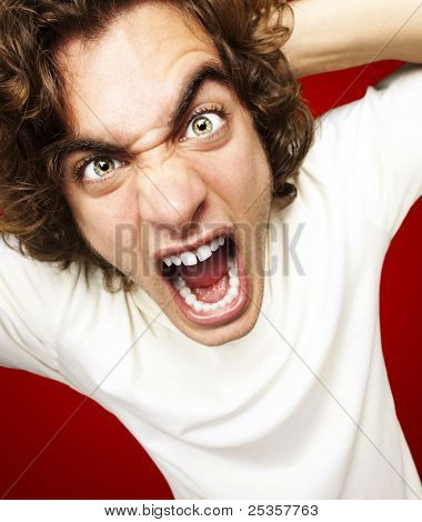portrait of furious young man shouting against a red background