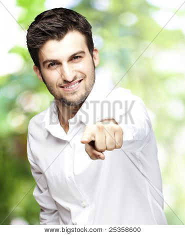 portrait of young man smiling and pointing with finger against a nature background