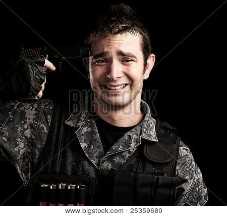 portrait of young soldier committing suicide against a black background