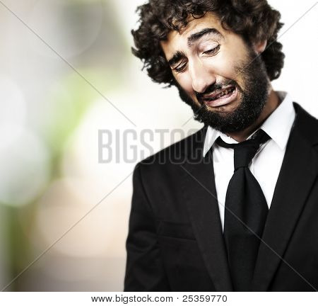 portrait of young business man with suit crying against a plants background