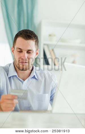 Young businessman with laptop and credit card in his home office