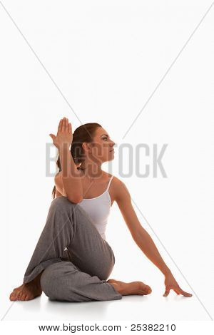 Portrait of a young woman in the Ardha Matsyendrasana position against a white background