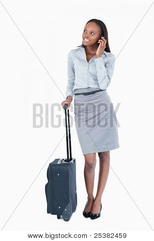 Portrait of a cute businesswoman with a suitcase making a phone call against a white background