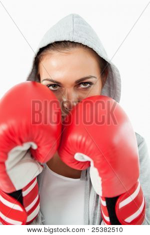 Female boxer with hoodie on in defensive stance against a white background