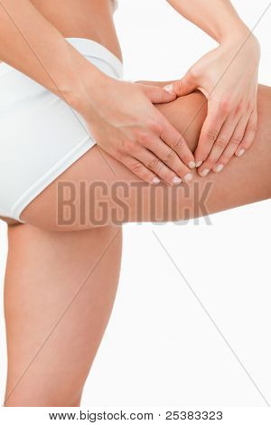 Portrait of a woman touching her thigh against a white background