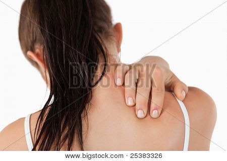 Back view of young woman with neck pain against a white background