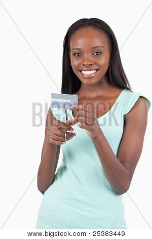 Happy smiling young woman destroying credit card against a white background