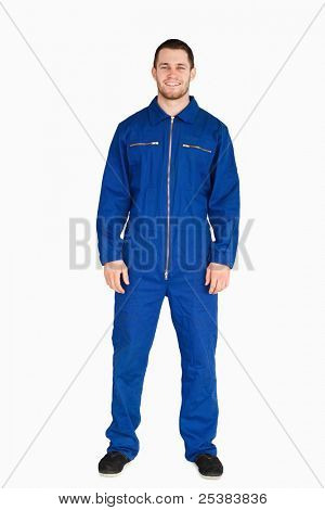 Young mechanic in boiler suit against a white background
