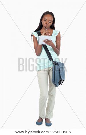 Joven estudiante tomando notas en su libreta de apuntes sobre fondo blanco