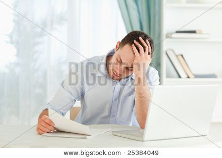 Young businessman reading an alarming letter