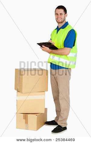 Side view of smiling young delivery man against a white background