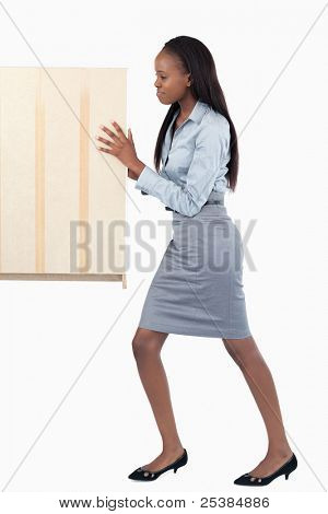 Portrait of a young businesswoman pushing a panel against a white background
