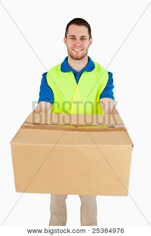 Smiling young delivery man handing over parcel against a white background