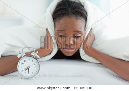 Tired woman covering her ears with a duvet while looking at her alarm clock
