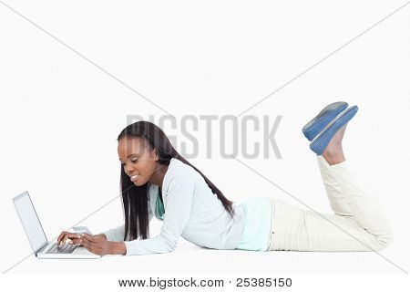 Side view of smiling woman lying on the floor working on her laptop against a white background