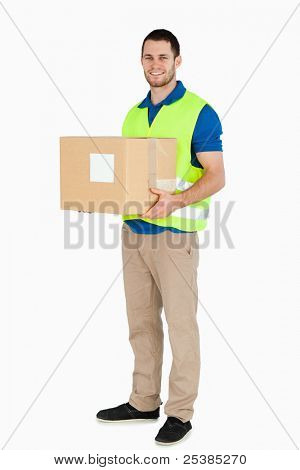 Smiling young delivery man holding a parcel against a white background