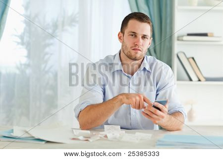 Young businessman using his electronic calculator