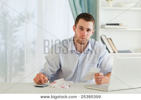 Young businessman checking bills in his home office