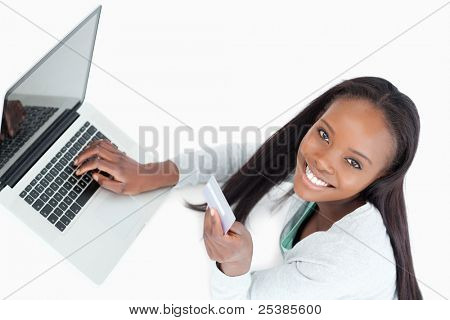 Smiling woman booking flight online against a white background