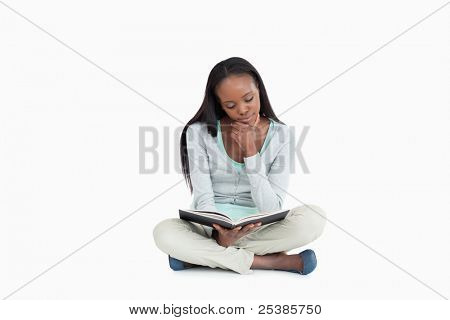 Young woman sitting on the floor reading in her book against a white background