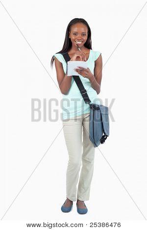Sonriente joven estudiante con libreta de apuntes sobre fondo blanco