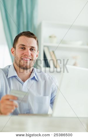 Young businessman with credit card and notebook in his homeoffice