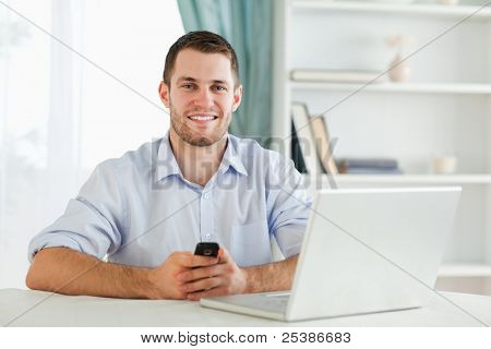 Smiling young businessman typing text message in his homeoffice