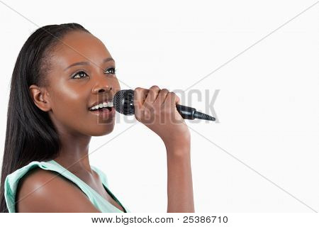 Woman with microphone singing against a white background