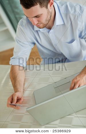 Young businessman with credit card on his notebook
