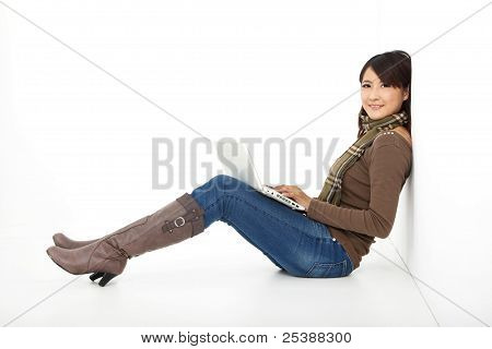 sonriente joven trabajando en un equipo portátil mientras está sentado en el piso