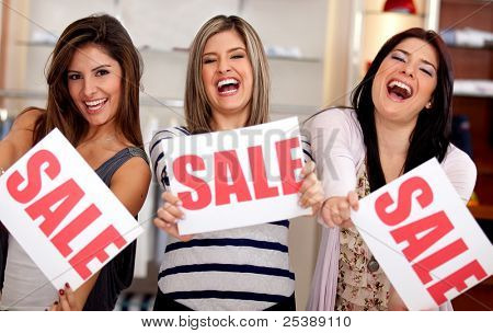 Saleswomen displaying sign of sale at a retail store