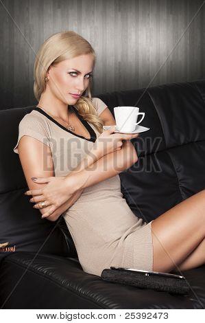 Sitzen auf dem Sofa aus einer Tasse trinken, sie schauen Sie In die Linse. Sie hat fesselnde Augen.
