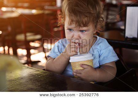 Süß traurig Kind Trinkwasser im Restaurant.
