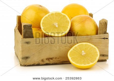 yellow and red grapefruit and a cut one  in a wooden box