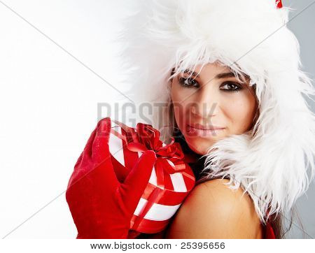 Christmas gifts. Woman wrapping christmas presents wearing santa hat.