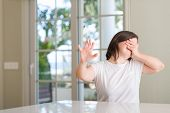 Down syndrome woman at home covering eyes with hands and doing stop gesture with sad and fear expres poster