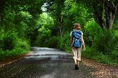 image of wet feet  - Woman with backpack walking on a wet road among green tropical trees - JPG