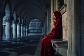 image of humility  - Woman in red cloak praying alone - JPG