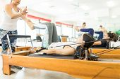 Pilates Instructor Assisting Young Woman On Reformer Machine In Gym poster