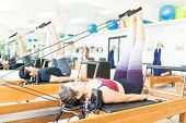 Determined Young Female Pulling Resistance Bands With Legs On Pilates Reformer In Gym poster